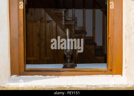lantern lamp light in wooden window on wooden old stairs background - Stock Photo