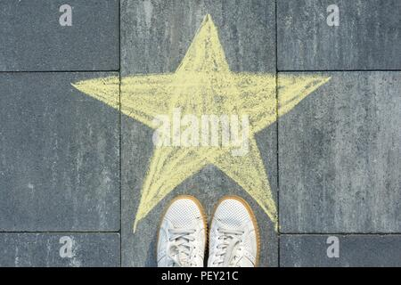 Drawing of crayons on the asphalt - star and feet of woman