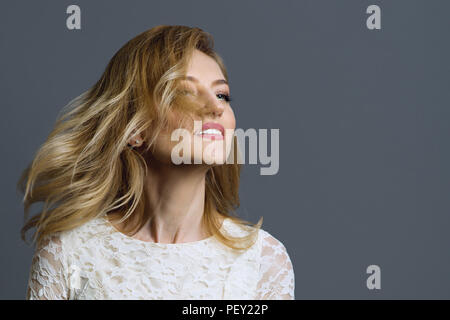 Portrait of a happy adult blonde woman spinning her head, grey background - Stock Photo