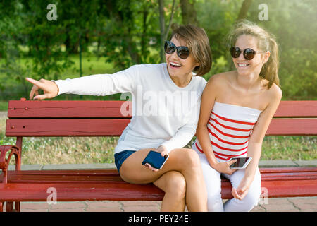 Mother and daughter teenager sitting on a bench in the park talking and enjoying themselves - Stock Photo
