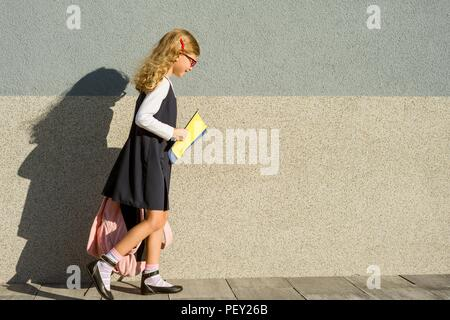 Back to school! Schoolgirl with notebooks in hand. A girl with a backpack goes to school. - Stock Photo