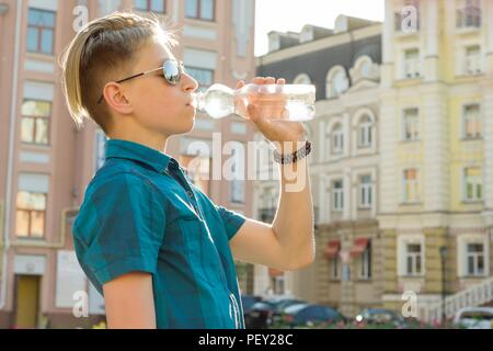 Teenager boy drinks water from bottle on sunny hot summer day in the city. - Stock Photo