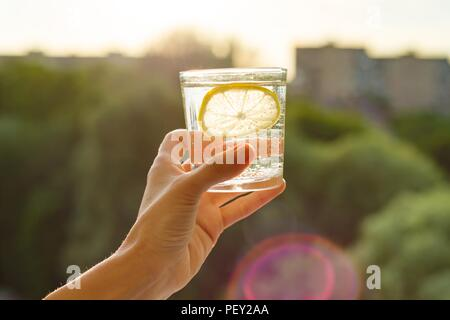 Glass of clear, sparkling water with lemon in hand. Background sky, silhouette of the city, sunset. - Stock Photo