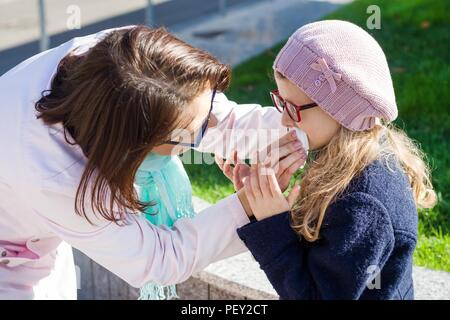 Mother wipes daughter's mouth with tissue paper. - Stock Photo