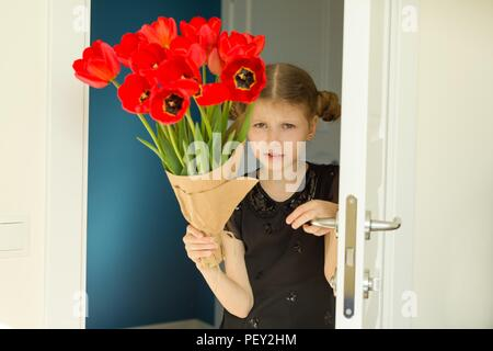 Beautiful little girl holding bouquet of flowers. Opens the door goes into the room - Stock Photo
