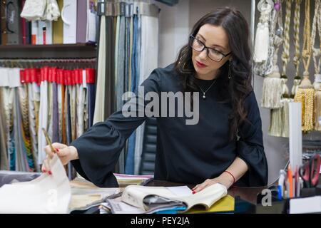 Woman owns a store of interior fabrics and decor works with samples of materials. Small business home textile shop - Stock Photo
