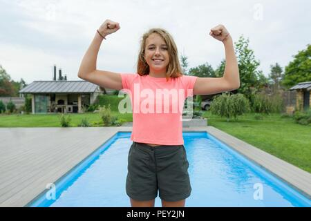 People, power, stamina, strength, health, sport, fitness concept. Outdoor portrait smiling teenage girl showing muscles, background swimming pool gree - Stock Photo