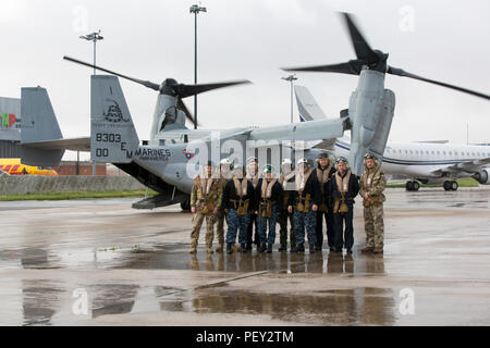 Multinational service members with Naval Striking and Support Forces NATO pose for a photo after completing a familiarization ride on board an MV-22 Osprey with Marine Medium Tiltrotor Squadron 263, Special-Purpose Marine Air-Ground Task Force-Crisis Response-Africa, at AT-1 Lisbon airport, Portugal, Feb. 11, 2016. SPMAGTF-CR-AF demonstrated the MV-22 Osprey's capabilities to STRIKFORNATO in order to familiarize other nations with capabilities for possible future military training and operations. (U.S. Marine Corps photo by Sgt. Kassie L. McDole/Released) - Stock Photo