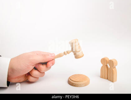 Two men and a hammer of the judge. The trial of cases in court, the resolution of a dispute between two people. Business relations, ascertaining the o - Stock Photo