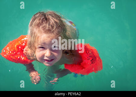 Funny cute little girl swims in a pool - Stock Photo
