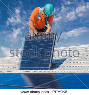 Man at work installing alternative energy photovoltaic solar panels on roof - Stock Photo