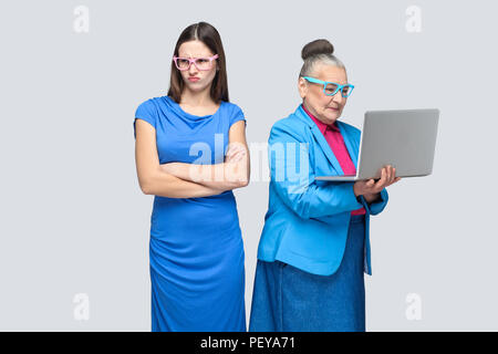 Unhappy confused granddaughter standing near grandmother holding and working on her laptop and making conflict. relationship or mutual understanding.  - Stock Photo