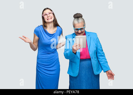 Why you did this? unhappy granddaughter woman standing near aged woman look in tablet. Relationship in the family. Granddaughter with grandmother. ind - Stock Photo