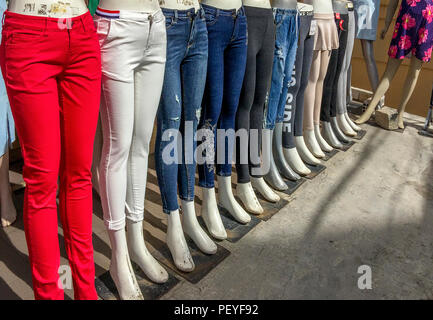 A row of mannequins outside a store in Vietnam with different colored jeans. - Stock Photo