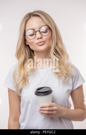 pleasant female is enjoying drinking coffe beverage. woman likes to drink coffe in the morning.white background - Stock Photo