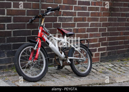 Childrens used old bike parked on cobblestone road in front of brick wall school building - Stock Photo