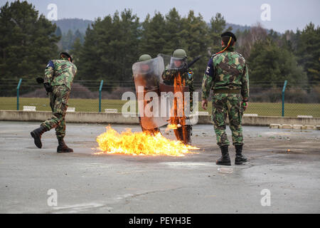 A Portuguese soldier, left, of Portuguese Military Police Battalion throws a Molotov cocktail at Romanian soldiers, center, of 26th Mountain Battalion while conducting fire phobia training during a Kosovo Force (KFOR) mission rehearsal exercise (MRE) at the Joint Multinational Readiness Center in Hohenfels, Germany, Feb. 17, 2016. The KFOR MRE XXI is based on the current operational environment and is designed to prepare the unit for peace support, stability, and contingency operations in Kosovo in support of civil authorities to maintain a safe and secure environment.  (U.S. Army photo by Sgt - Stock Photo