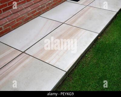 Modern stone slabs laid around garage block, shows detail of stone slab fittings around traps or doors - Stock Photo