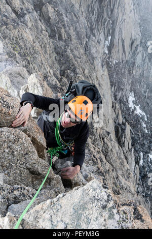 A climber on the traverse of the Aiguille d'Entrees - Stock Photo