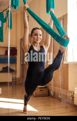 young,positive,beautiful woman is doing stretching splits with hammock in the modern gym. development of flexibility - Stock Photo