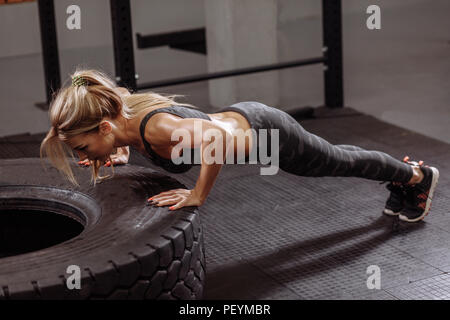 hardworking young pleasant woman is doing exercise for abs. side view full length photo - Stock Photo