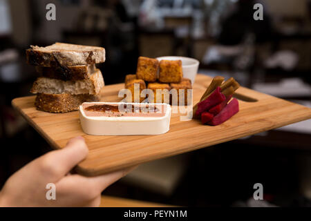 A European style appetizer platter consisting of chicken liver mousse, polenta fritters, bread, and pickled carrots. - Stock Photo