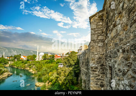 The river Neretva flows by the ancient wall surrounding the old town section of Mostar, Bosnia - Stock Photo
