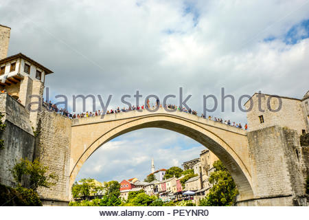 A local Bosnian prepares to jump off the Stari Most, the old bridge in Old Town Mostar, Bosnia and Herzegovina as tourists gather to watch the event - Stock Photo