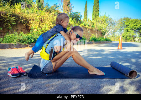 Sportive mother with child outdoors doing fitness excercise,  happy family together on workout, active healthy lifestyle - Stock Photo