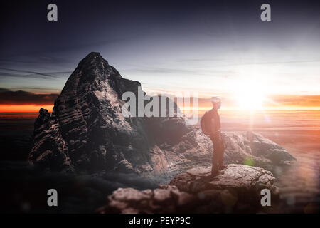 Dramatic and inspirational landscape with the silhouette of a hiker standing on the top of a mountain peak looking at the horizon at sunset - Stock Photo