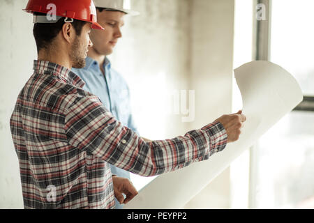 handsome beaded architect is discussing the idea of a new house with a client in the bright room - Stock Photo