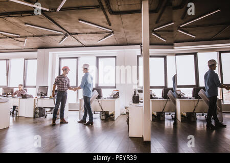 two architects are greeting each other at workplace. salute and welcome concept - Stock Photo