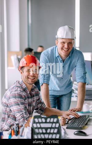 handsome smiling architects working in the office building. workers with good mood. close up portrait - Stock Photo