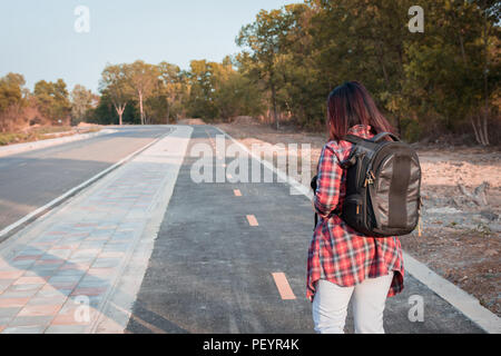 Travel concept. Traveling woman with backpack walking on asphalt road countryside - Stock Photo
