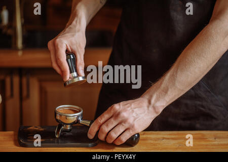 a barista is using a tamper to press coffee seads. close up cropped shot - Stock Photo