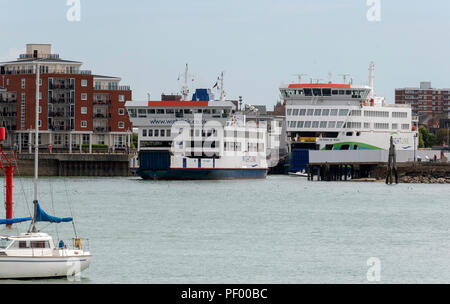 Portsmouth Car Ferry terminal, Gunwharf, Portsmouth, England. Roro ferry St Faith leaving her Portsmouth dock bound for the Isle of Wight. On the quay is Victoria of Wight tthe new Wightlink flagship to come into service - Stock Photo