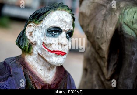 Saterland, Germany. 18th Aug, 2018. The wooden film character Joker stands on a pedestal during the Northwest German championship in chainsaw carving. A figure is carved out of wood with a chain saw during the discipline of speed carving. The wooden figures created in this way are auctioned off for a good cause. Credit: Hauke-Christian Dittrich/dpa/Alamy Live News - Stock Photo