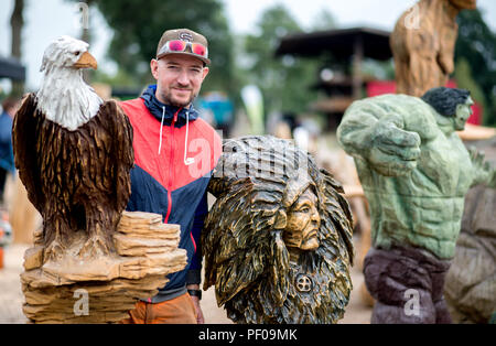Saterland, Germany. 18th Aug, 2018. Wood artist and organizer Steffen Merla stands next to several wooden figures he made during the Northwest German Championship in chainsaw carving. A figure is carved out of wood with a chain saw during the discipline of speed carving. The wooden figures created in this way are auctioned off for a good cause. Credit: Hauke-Christian Dittrich/dpa/Alamy Live News - Stock Photo