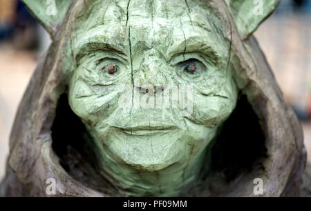 Saterland, Germany. 18th Aug, 2018. The wooden film character Yoda from the film Star Wars stands on a pedestal at the Northwest German championship in chainsaw carving. A figure is carved out of wood with a chain saw during the discipline of speed carving. The wooden figures created in this way are auctioned off for a good cause. Credit: Hauke-Christian Dittrich/dpa/Alamy Live News - Stock Photo