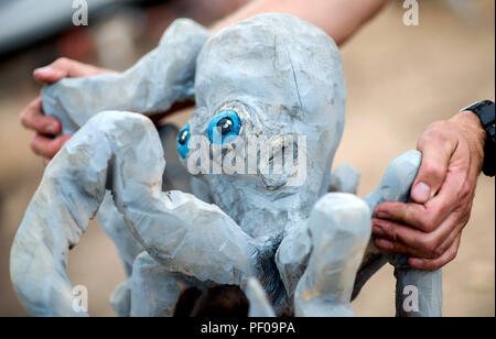 Saterland, Germany. 18th Aug, 2018. A wood artist puts a figure of an octopus made of wood on a pedestal during the Northwest German championship in chainsaw carving. A figure is quickly carved out of wood with a chain saw during the discipline of speed carving. The wooden figures created in this way are auctioned off for a good cause. Credit: Hauke-Christian Dittrich/dpa/Alamy Live News - Stock Photo