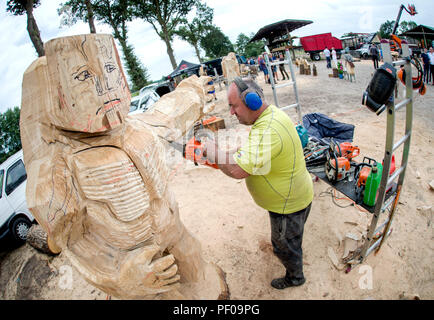 Saterland, Germany. 18th Aug, 2018. Wood artist Bernd Voigt from the Erzgebirge is working on a large wooden figure during the Northwest German championship in chainsaw carving. A figure is quickly carved out of wood with a chain saw during the discipline of speed carving. The wooden figures created in this way are auctioned off for a good cause. Credit: Hauke-Christian Dittrich/dpa/Alamy Live News - Stock Photo