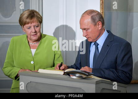 Gransee, Germany. 18th August 2018. Russia's President Vladimir Putin (R) signs a distinguished visitors' book as he meets with German Chancellor Angela Merkel at a reception house at Schloss Meseberg. Alexei Druzhinin/Russian Presidential Press and Information Office/TASS Credit: ITAR-TASS News Agency/Alamy Live News - Stock Photo