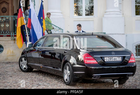 Meseberg, Germany. 18th Aug, 2018. German Chancellor Angela Merkel of the Christian Democratic Union (CDU) walks outside Meseberg Palace to meet Russian President Vladimir Putin, who arrives in a limousine. Credit: Michael Kappeler/dpa/Alamy Live News Credit: dpa picture alliance/Alamy Live News - Stock Photo