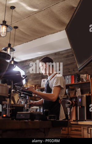 close up back view photo of a young man making cappuccino in the coffee bar with stylish interior - Stock Photo