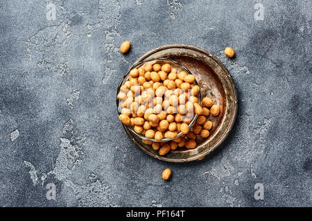 Spicy coated fried peanuts on gray background. Top view of snacks and nuts. - Stock Photo