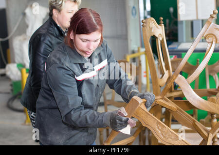 Belarus, the city of Gomel, on April 26, 2018. Furniture factory. The employee of the furniture department polishes the chair with a sandpaper. Furnit - Stock Photo