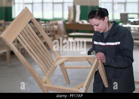 Belarus, the city of Gomel, on April 26, 2018. Furniture factory. The employee of the furniture department polishes the chair with a nazhdachka. Furni - Stock Photo