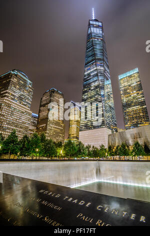 One WTC shines brightly in the background of the 9/11 Memorial in Lower Manhttan, New York City. - Stock Photo