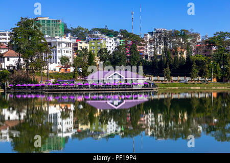 Beautiful scenic reflections on the lake at Da Lat with cityscape background and blue sky. - Stock Photo