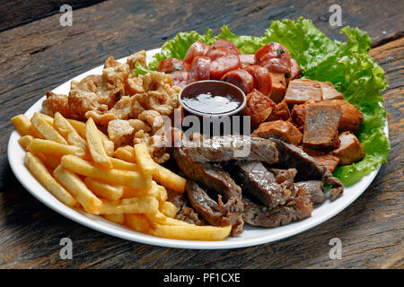 Snacks with fries, crackers, meat, pork, sausage and babercue sauce - Stock Photo